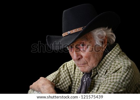 Old man wearing a black cowboy hat and green and white checked shirt staring into camera isolated on black - stock photo