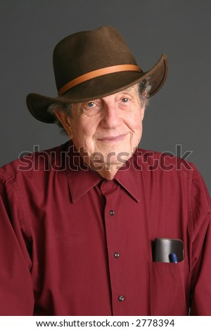 Old man wearing red shirt and Australian stockman's hat with dark background