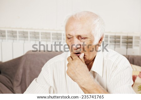 Old man wearing white shirt in thoughts sitting on the sofa - stock photo