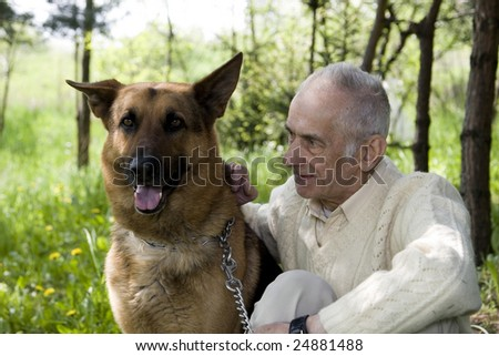 Old man who is sitting in the park and training his dog. - stock photo