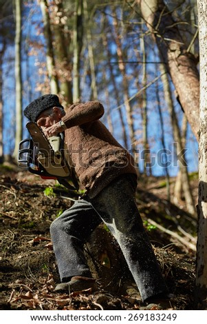 Old man with a chainsaw going to a tree to cut it down - stock photo
