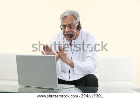 Old man with a laptop chatting online - stock photo