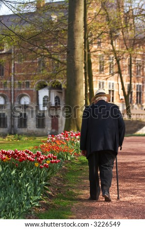 Old man with a walking stick in a springtime castle garden - stock photo