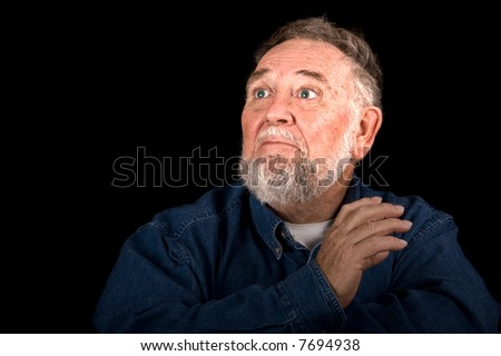 old man with face illuminated, scared or surprised look, looking into black copy space - stock photo
