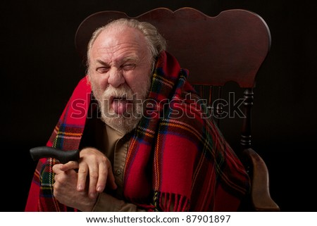 Old man with gray beard with bright red plaid shawl sits hunched over his cane and sticks out his tongue. Head and shoulders portrait in a low key horizontal image. - stock photo