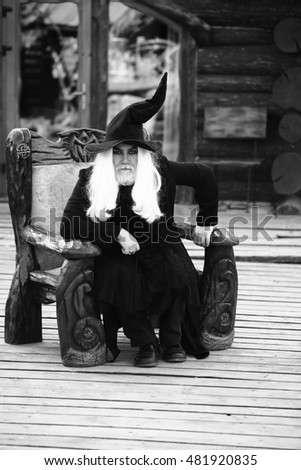 Old man with long grey hair beard in wizard costume and hat for Halloween sits in wooden chair black and white on log house background