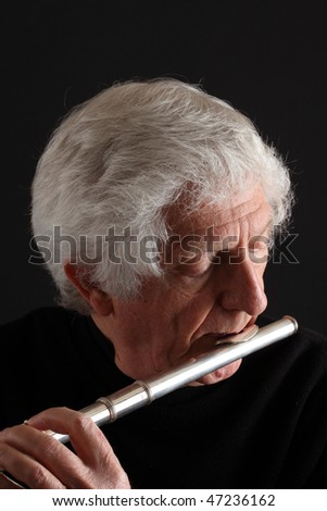 Old man with long white hair playing a silver flute against a black background - stock photo