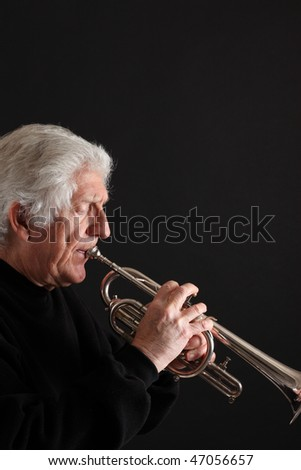 Old man with long white hair playing a silver trumpet against a black background - stock photo