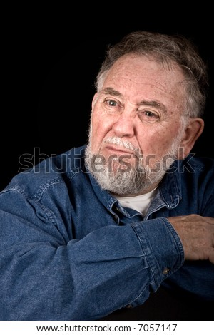 old man with look of anger or betrayal, isolated over black - stock photo