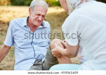 Old man with pain on his knee and woman gives him first aid - stock photo