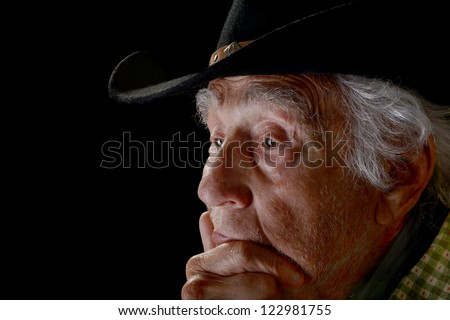 Old man with serious look on face wearing a black cowboy hat isolated on black - stock photo