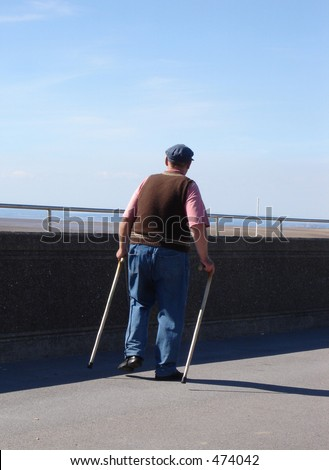 Old man with two walking sticks - stock photo