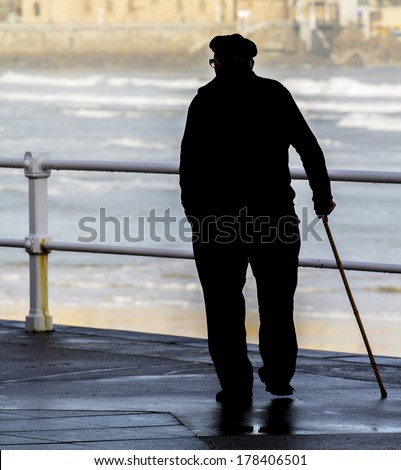 Old man with walking stick - stock photo