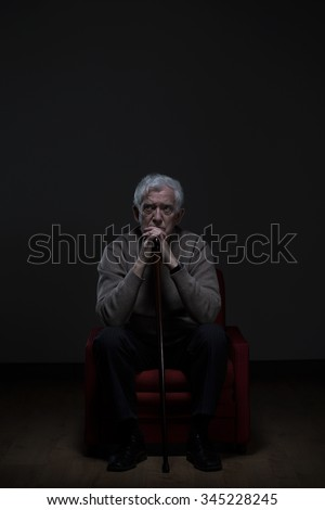 Old man with worried face sitting alone and holding cane - stock photo