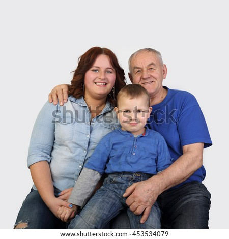 Old man, woman and little boy - Three generations of one family - Grandfather, mother and son portrait on gray background in square - stock photo
