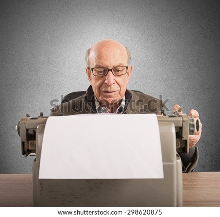 Old man writes letters with his typewriter - stock photo