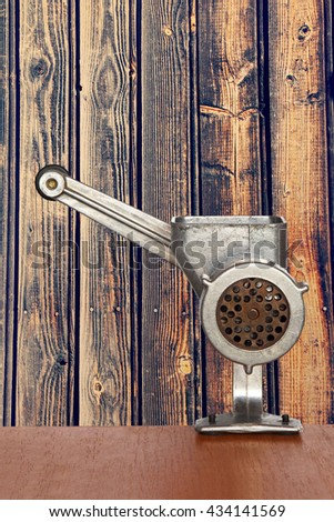 Old manual meat grinder on wooden timber wall background taken closeup. - stock photo