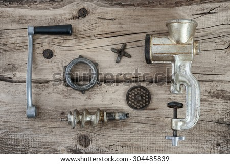 Old manual meat grinder unassembled on a wooden table - stock photo