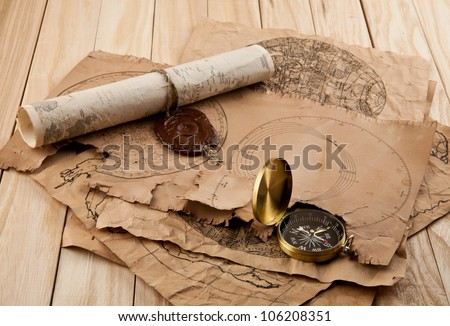 old maps and compass on a wooden table - stock photo