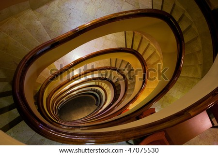 Old marble spiral stairs with wooden handrails - stock photo