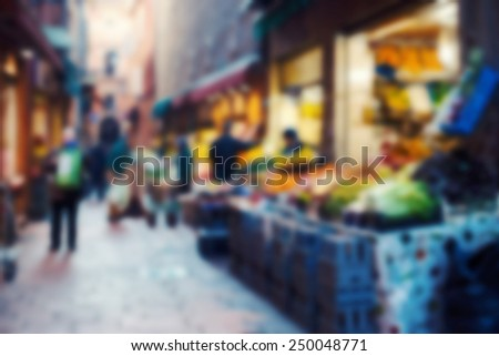 Old market in italian city. Blurred and filtered image with unrecognizable people. - stock photo