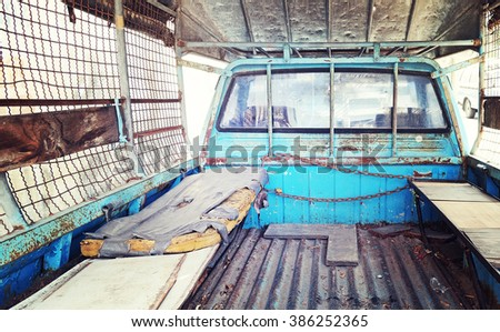 Old mattress place behind back of blue pickup truck in vintage retro style color - stock photo