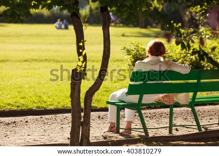 Old mature woman female sitting on bench relaxing in park. - stock photo