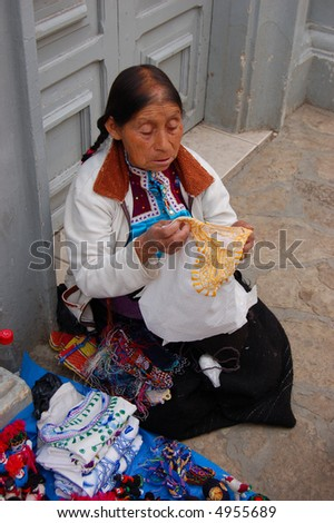 Old Mayan Woman selling shirts on the street - stock photo