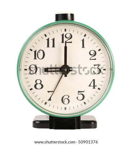 Old mechanical alarm clock with a round dial on a white background