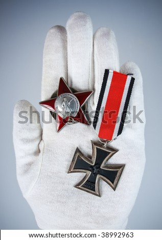 "Old medals german ""Iron Cross"" and soviet ""Red Star"" in hand - stock photo"