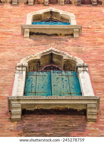 Old, medieval arched windows with blue and green shutters in Venice, Italy, perspective, low angle view. - stock photo