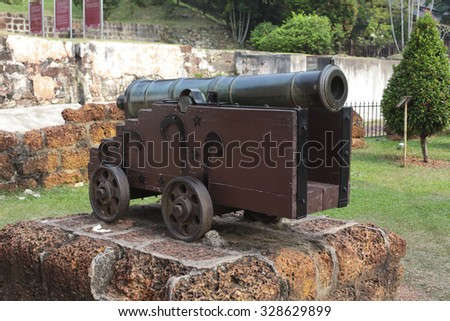 Old medieval artillery canon before a brick wall.