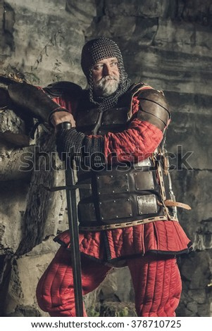 Old medieval King in armor with sword on the rocks background. Artistic toning. - stock photo