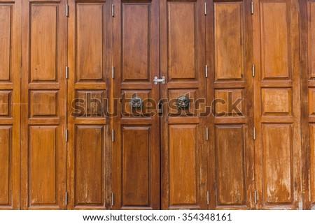 Old medieval metal handles on antique dark wooden door - stock photo
