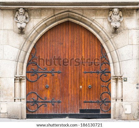 Old medieval wooden door with metal motif decoration in Paris, France - stock photo