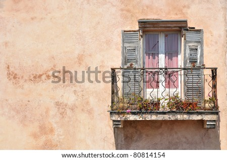 Old mediterranean window with structured wall - stock photo