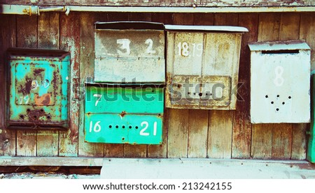 Old memory mailboxes concept. Multicolored old shabby mailboxes with numbers of people's memories houses over wooden scuffed background. Outdoor shot. Copy-space. - stock photo