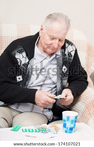 old men holding a medicine pill at home - stock photo