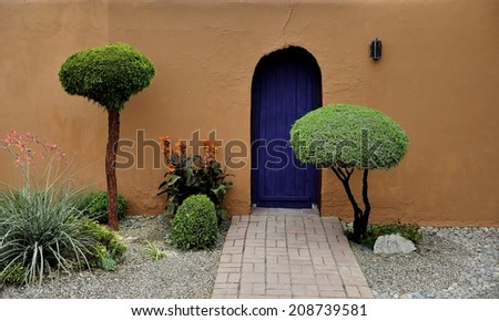 Old Mesilla New Mexico House made of terra-cotta with a brilliant blew door and tradition New Mexico Landscaping of green succulents - stock photo