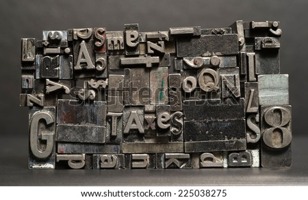 Old metal blank printing press typeset all stacked up saying taxes - stock photo
