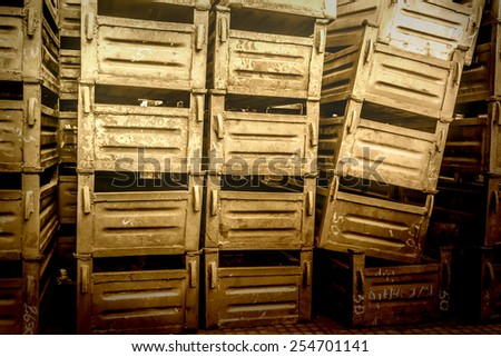 Old metal boxes stacked in storehouse of factory - stock photo