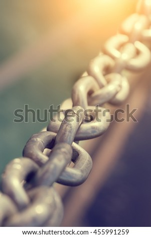Old metal chain on a blurred background. Toned - stock photo