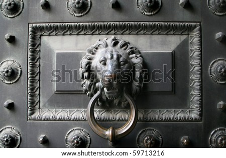 Old metal door with a lion head as a knocker - stock photo