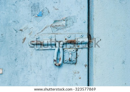 Old metal door with chipped blue paint and rusted lock. - stock photo