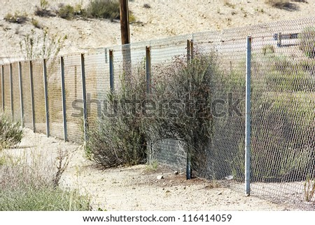 Old metal fence near a desert road - stock photo