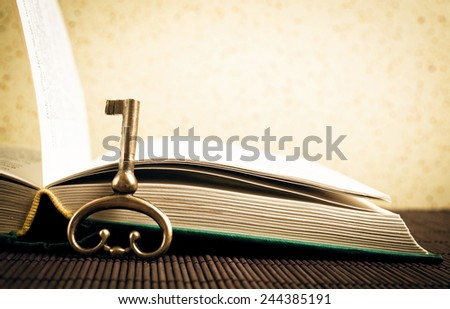Old metal key and open book - stock photo