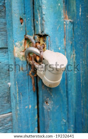 old metal lock on the wooden door - stock photo
