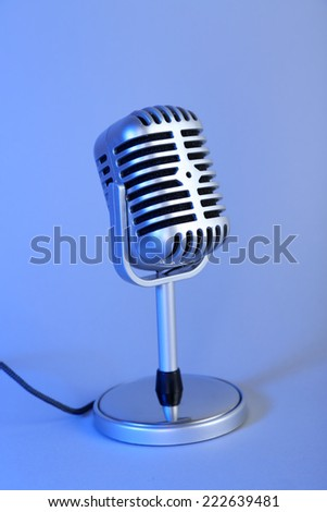 Old metal microphone on light blue background - stock photo