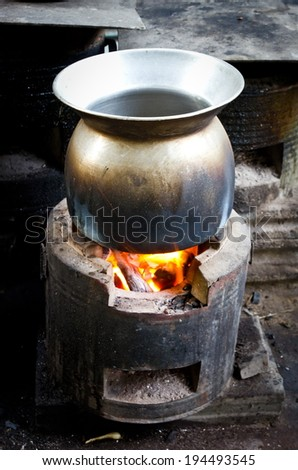 Old metal pot on the fire - stock photo