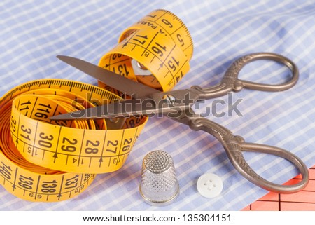 Old Metal Scissors, Tailor Tape Measure and Metal Thimble on Fabric